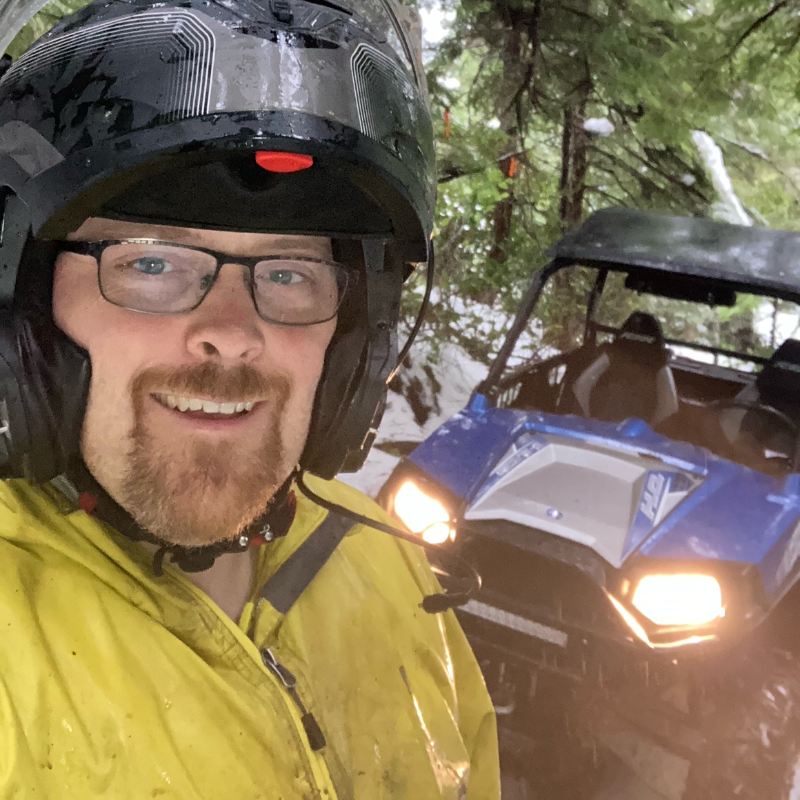 Dillon Baycroft wears a yellow jacket, black rimmed glasses and a black helmet in front of his blue side-by-side ATV with its lights on.