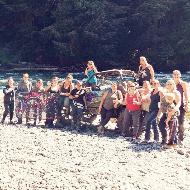 A large group of women stand on a sandy beach in front of and on top of an ATV side-by-side. Chipmunk River flows in the background.