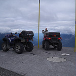 Two quads parked on a platform overlooking a mountain range.