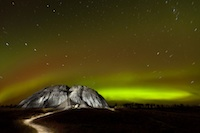 An amazing view of the the northern lights, stripes of yellow and green, over a small mountain.