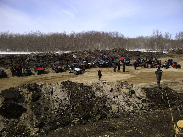 A picture of ATVers all standing around their machines waiting for the 1st ride of the season.  There are sand dunes behind them, and in the foreground.