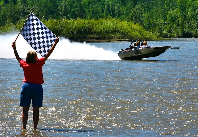 In the forground there is a women standing ankle deep in the water with a checkered flag at the finish line.  On the lake a boat is speeding past.