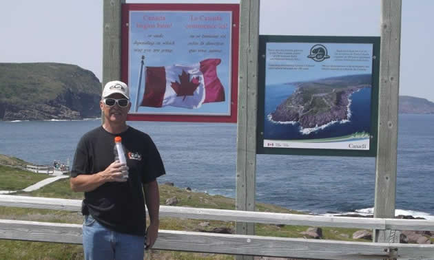 A man standing by a sign at Cape Spear, Newfoundland.