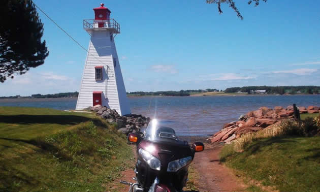 A motorcycle parked by a red and white lighthouse.