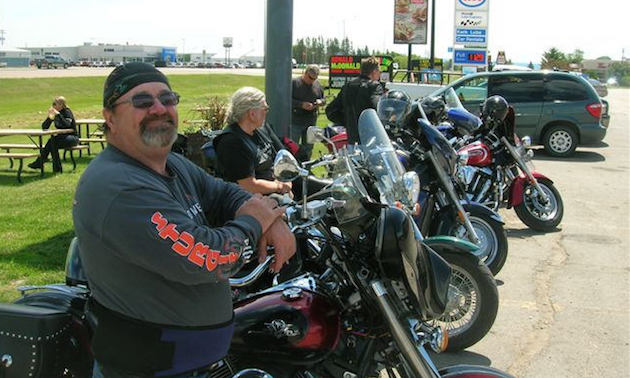 A line up of bikers stopped at a gas station.