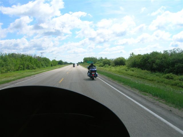 A photo taken from behind a bikers windshield, looking at two bikes on the highway in front of it.