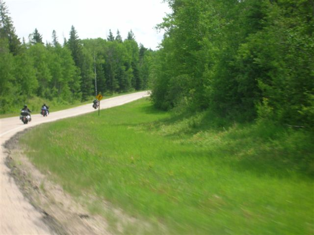 A photo of a curve in the road and three bikes on the highway off in the distance.