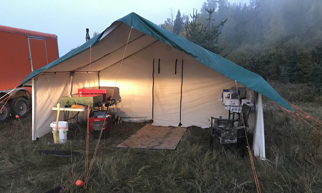 While setting the tent takes less than an hour, full set-up with bunks, sleeping bags and mattresses,  lanterns, stove and table takes closer to three hours. Note the 3 metre (10-foot) porch allows a covered area to keep firewood dry and to wash dishes out of the elements.