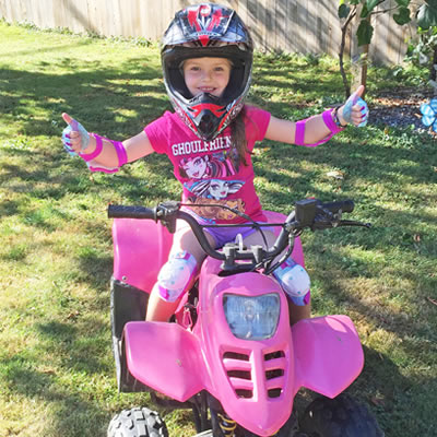 Five-year-old Lyla Pylatuk sits on her hot pink quad.
