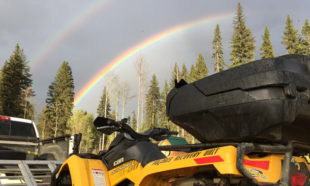 A double rainbow is shown, with a UTV parked in the foreground.