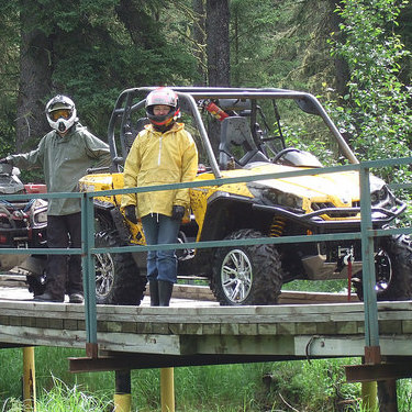 3 quadders stopped on a wooden bridge in the Lakeland Provincial Recreation Area.