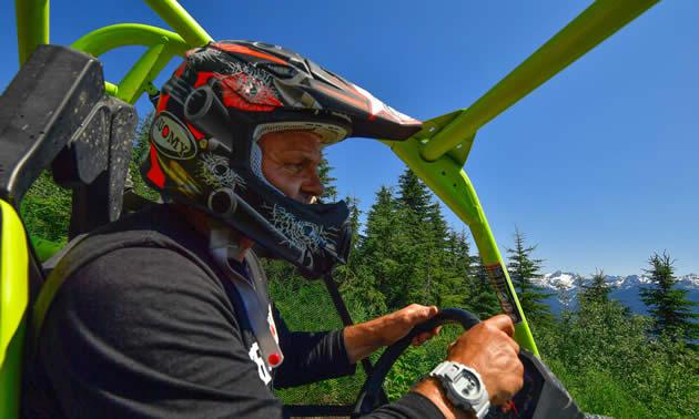 Daniel Kellie, owner of Glacier Mountain Resort, riding in his ATV