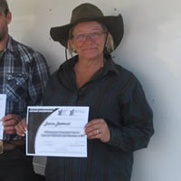 A woman in and a man smile and hold up certificates while a man in a white shirt stands next to them.