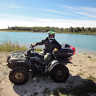 a man standing beside an ATV in front of a lake