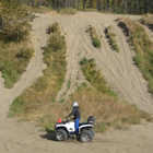 A ATV rider sits at the bottom of a dune looking up at the trails and the blue sky.