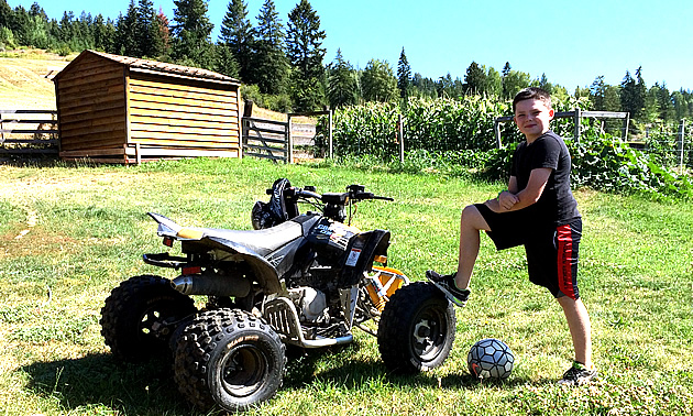Eric Buckley standing next to his Can-Am quad with a soccer ball in a field next to a garden in the Pend d'Oreille.