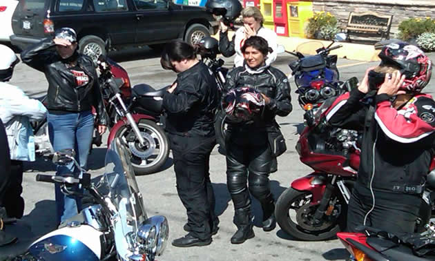 women in motorcycle garb mingle around their parked bikes.