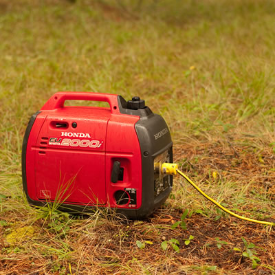 A black and red Honda generator sitting on grass.