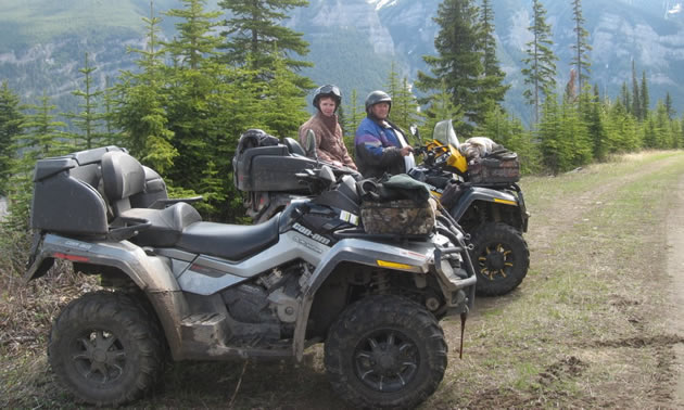 Gordon and his wife sit on a yellow quad against a scenic backdrop.