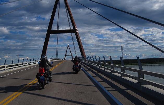 Janna Graham (left) and Robin Weber ride across the Deh Cho Bridge.