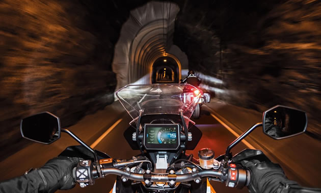 Picture from driver's perspective, showing dashboard of bike, and driving through dark tunnel.