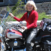 Middle-aged blond woman sits astride a Harley Davidson motorcycle