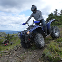 Someone on a blue ATV descends down a steep shale slope while a group looks on.