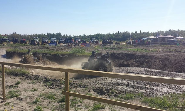 Two ATVs race on a muddy track.
