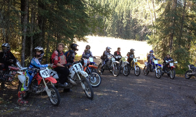 A row of riders on off-road bikes are lined up on a gravel drive in front of trees and a lake.