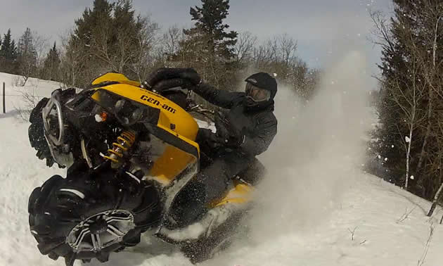 A man on a yellow ATV does a catwalk leaving a cloud of snow behind him.