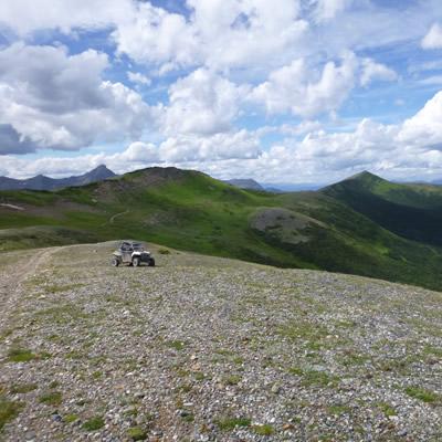ATV sitting on summit of mountain.