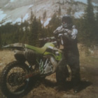 A young man stands in front of forest a mountains with a lime green dirt bike.