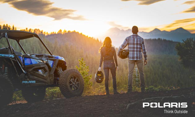 Two people standing side-by-side, looking at sunset, with ATV beside them.