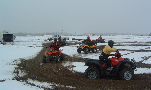 Group of people riding ATVs in snowy field, practicing manoeuvres.