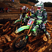 Two riders on bright green bikes try to navigate over a pile of logs.