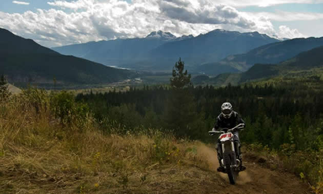 A man on a dirt bike comes around the corner with a view panorama of mountains behind him.