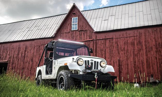 White Roxor parked beside red barn.