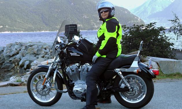 A woman sits on her black Harley-Davidson alongside a lake.
