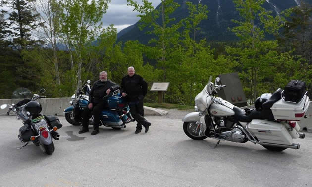 A man with white hair and beard sits on a blue road king motorcycle while another man stands next to him. Two other bikes are in the foreground.