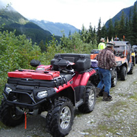 A group of ATVs lined up on a trail.