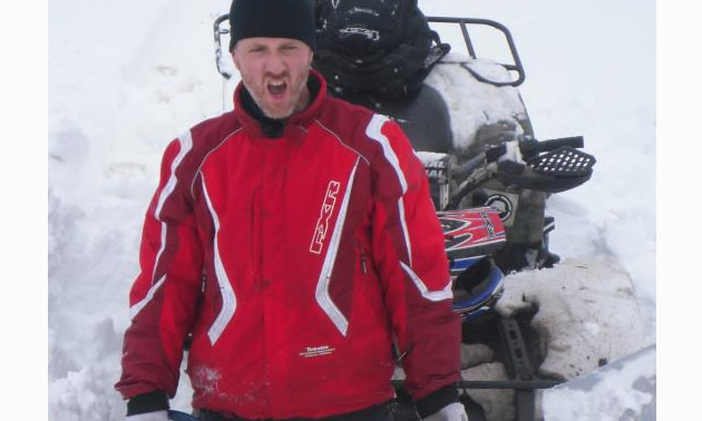 man standing in the snow with his quad