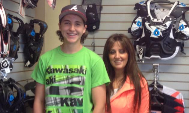 Brayden & Nikki standing next to eachother in a motorcycle shop.