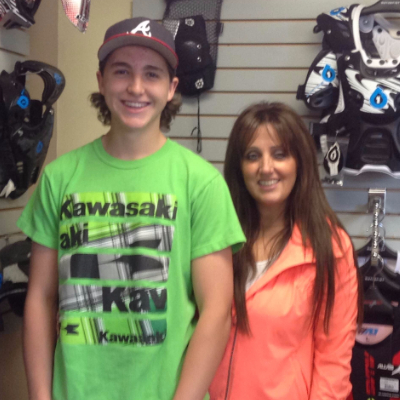 Brayden & Nikki standing next to eachother in a motorcycle shop.