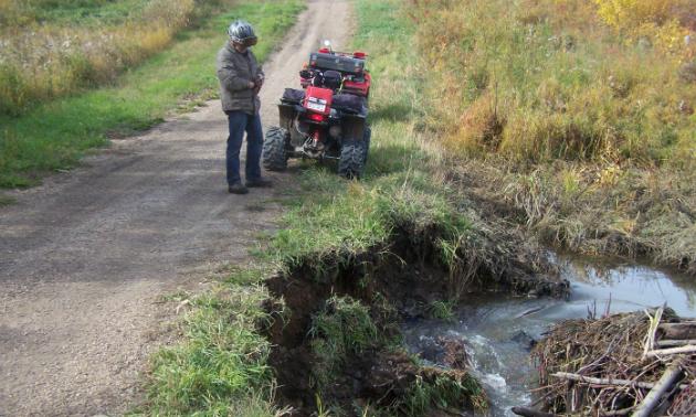 Trail Steward Robert Pruneau assesses the trail condition.
