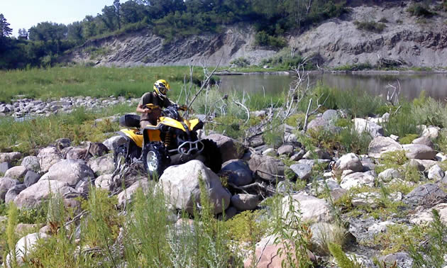 A rider on a yellow quad navigates through a field of boulders. Behind him is a rolling green hill.