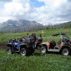 Two ATVs and a Razor are parked in an expanse of green field with a mountain off in the distance.