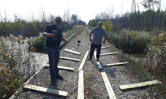 The ATV club members are installing safety railings between the trail and the wetlands.