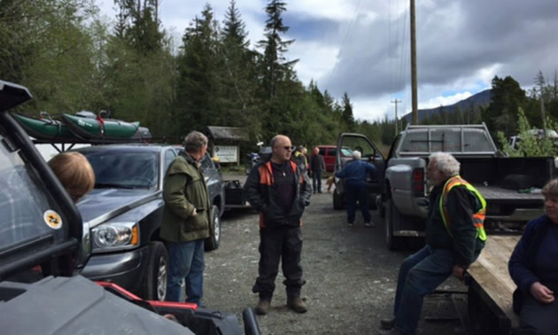Members of the Alberni Valley Hill Climbers are standing around and discussing details at the trailhead to Virgin Falls.
