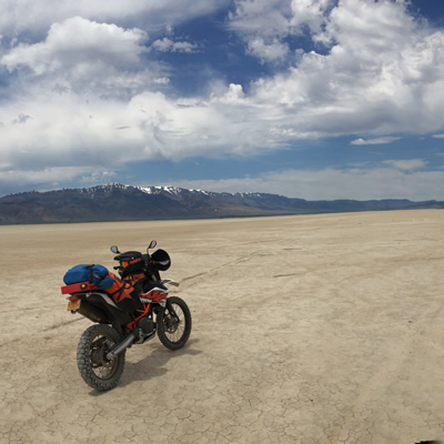 A panorama of the Alvord desert with a dual sport bike in the photo.