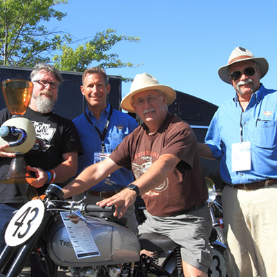 Picture of motorcycle enthusiasts, (one sitting on a motorcycle) and man holding trophy.